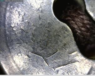 50X: Nappi on varhaista muovia ja se on alkanut näyttää hajoamisen merkkejä.