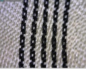 50X: Hihavuorikangas näyttäisi olevan nelivartista loimipomsia kuosiin kudotulla raidalla. Kuitu on luultavasti muuntokuitua.